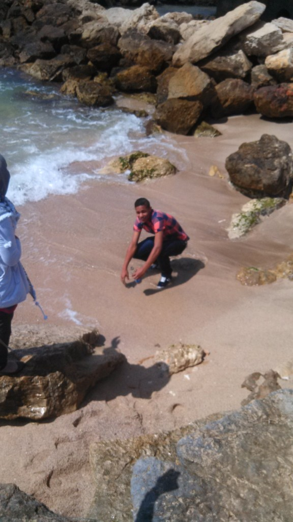 Khalil, 15, collecting sand and sea water in a bottle, Haifa